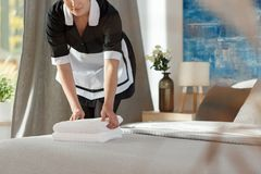 Chambermaid preparing hotel room. Close-up of chambermaid in uniform with towels preparing hotel room for guest`s arrival royalty free stock photos