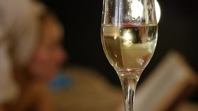Close-up champagne flows into a glass. Beautiful young girl resting comfortably on a bed and reads a book. slow motion. Close-up champagne flows into a glass stock video footage