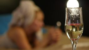 Close-up champagne flows into a glass. Beautiful young girl resting comfortably on a bed and reads a book. slow motion. Close-up champagne flows into a glass stock video