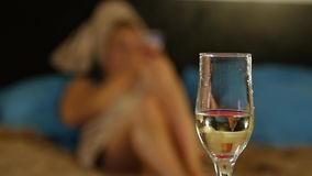 Close-up champagne flows into a glass. Beautiful young girl resting comfortably on a bed and reads a book. Close-up champagne flows into a glass. Beautiful stock video footage