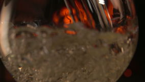 Close-up Champagne is poured into a glass on a background of fire stock footage
