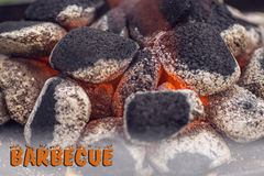 Close up of charcoal briquettes ready for barbecue grill, background with letters Stock Image