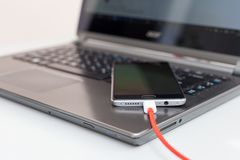 Close-up of charging a smartphone from a laptop Stock Photography