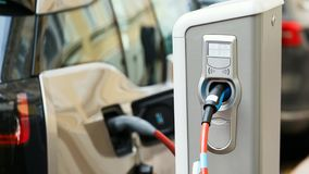 Close up of charging station. A cable is connected to the station, which charges an electric car. Camera moves forward. 4k video stock footage