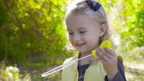 Close-up of a charming blond girl staying in sunrays and blowing soap bubbles. Little child with brown eyes playing in. The park and smiling stock video footage