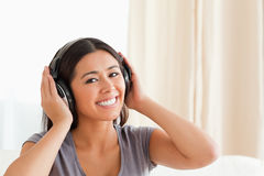 Close up of a charming woman. With earphones looking into camera in livingroom Stock Photo