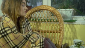 Close-up of a charming young girl is wrapped in a blanket and goes to bed at home in Wicker Chair stock video