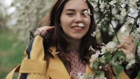 Cheerful young sweet girl with flower petals in her hair on a walk among the flowering trees. Spring mood. Close-up