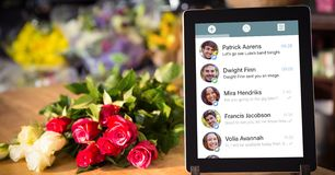 Close-up of chat list on digital tablet by flower at table Royalty Free Stock Image
