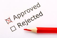 Close up check boxes approved or rejected with red pencil on white paper. Approved checkbox is checked. stock photo
