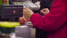 Woman working on cash register in the store. Close up check out counter. Rear view of hands of woman working on cash register in the supermarket stock footage