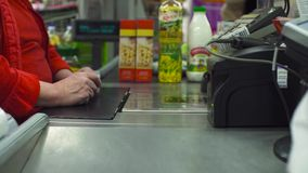 Senior woman working on cash register. Close up check out counter. Senior female hands working on cash register in the supermarket stock footage