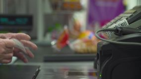 Senior woman working on cash register. Close up check out counter. Senior female hands working on cash register in the supermarket stock video footage
