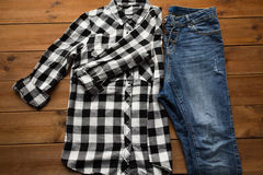 Close up of checkered shirt and jeans on wood Royalty Free Stock Photos