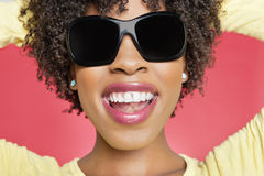 Close-up of a cheerful African American woman wearing sunglasses over colored background Royalty Free Stock Images