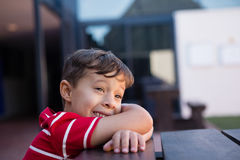Close up of cheerful boy looking away. While leaning on table at home Stock Images