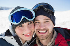 Close up of a cheerful couple with ski goggles on snow Royalty Free Stock Image