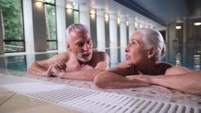 Happy mature couple relaxing on pool side indoors stock video footage