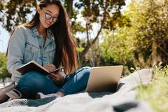 Happy girl studying in a park stock photos