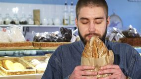 Close up of a cheerful man smelling freshly baked bread. Close up shot of a handsome bearded young man smiling happily smelling freshly baked delicious bread stock footage
