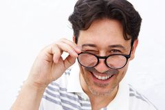 Cheerful mature man holding glasses and winking Royalty Free Stock Photography