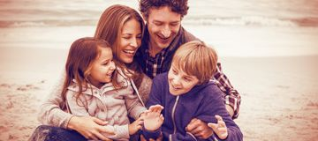 Cheerful parents with children at sea shore royalty free stock photo