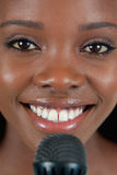 Close up of cheerful smiling female singer. With microphone Stock Photos