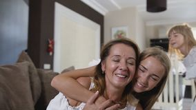 Close up of cheerful teen girl with long hair in white dress is hugging beautiful mum and laughing in the living room at. Home. Happy moments. Beautiful woman stock video footage