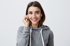 Close up of cheerful young attractive dark-haired caucasian girl in casual gray hoodie smiling brightly, holding Stock Images
