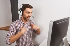 Close up of cheerful young funny good-looking male gamer playing online games on personal computer in headphones with. Microphone, pointing at himself with Royalty Free Stock Images
