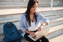 Close-up of cheerfull asian female student, holding laptop, chec. King time, sitting on the stairs Royalty Free Stock Image