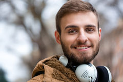 Close up of cheerul attractive bearded young male with headphones Royalty Free Stock Images