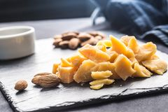 Close-up Cheese pieces and nuts on slate board royalty free stock images