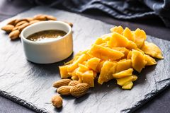 Close-up Cheese pieces and nuts on slate board royalty free stock image