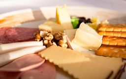 Close up of Cheese platter. With different cheese, crakers, ham, nuts, salami, avocado and rum raisins Royalty Free Stock Photography