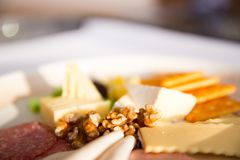 Close up of Cheese platter. With different cheese, crakers, ham, nuts, salami, avocado and rum raisins Stock Photos