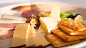 Close up of Cheese platter. With different cheese, crakers, ham, nuts, salami, avocado and rum raisins Stock Image