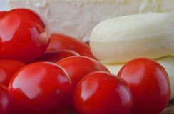 Close up of cheese and tomato. Close up of cheese and a tomato on trencher, wood background Stock Photography