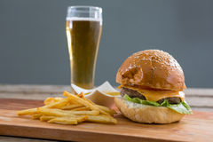 Close up of cheeseburger with french fries and beer glass. At table against wall Stock Photo