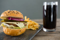 Close up of cheeseburger with french fries and drink. On slate at wooden table Stock Photography