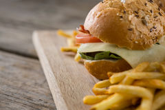 Close up of cheeseburger with french fries. Served on cutting board Royalty Free Stock Photo