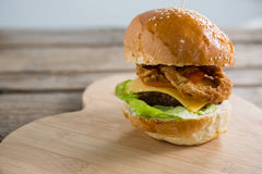 Close up of cheeseburger with onion rings. On cutting board Stock Photography