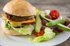 Close up of cheeseburger with salad and french fries. Served in plate on table Stock Photo
