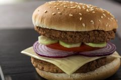 Close up of a cheeseburger with tomato, onion and cucumber. On slate Stock Photos