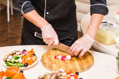 Close-up of chef cooking food kitchen restaurant cutting cook hands hotel man male knife preparation fresh preparing Royalty Free Stock Photo
