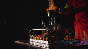 Close-up of chef cooking a main banquet dish. Vegetables and meat with fire show. In slow motion. Meat in fire flame. Cook pours burning alcohol on meat stock footage