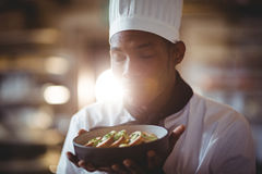 Close-up of chef with eyes closed smelling food. In the kitchen Stock Photos
