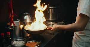 Close-up of a chef preparing a dish in a frying pan. Oil and alcohol ignite with an open flame in slow motion 4k