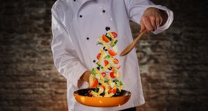 Close-up of chef preparing italian pasta meal. Concept of flying food. Very high resolution image Royalty Free Stock Photos