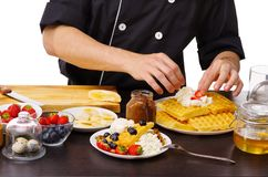 A close-up of the chef`s hand imposes a strawberry on the waffles. stock image